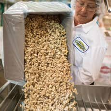 Team member pouring walnuts into the vat
