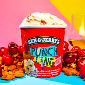 An open pint of Punch Line™ Ice Cream in front of a pile of cherries and almounds