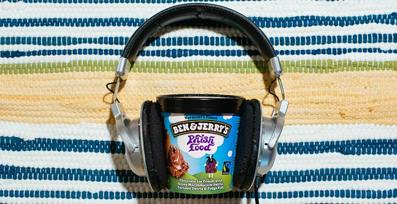 a Pint of Ben & Jerry's Phish Festivals with headphones on