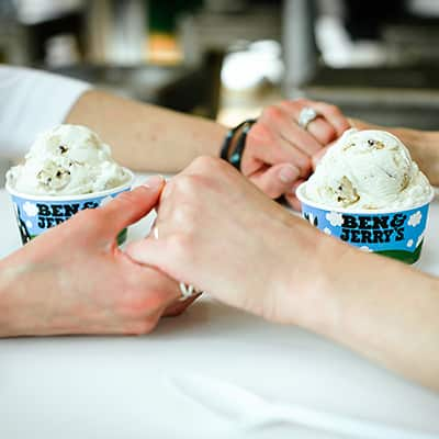 Couple holding hands at a Ben & Jerry's ice cream shop.