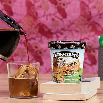 A pint of ice cream a glass with ice cream and coffee being poured over it
