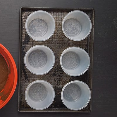 6 baking cups on a baking sheet