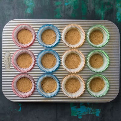 Muffin pan with graham cracker crumbs in cups