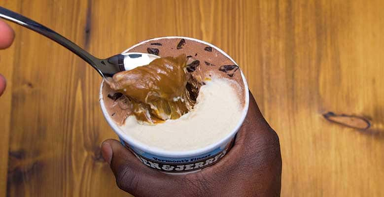 Pint of Ben & Jerry's, hand digs into center of ice cream
