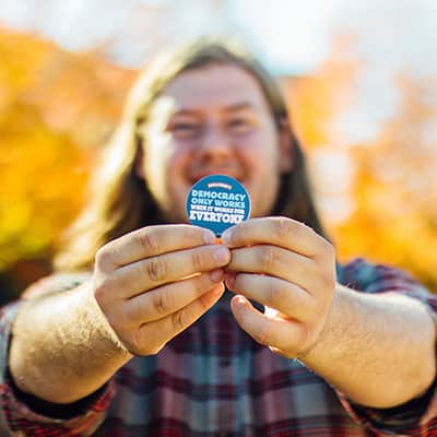 Man holding a button stating he registered