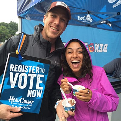 A couple with a register to vote sign