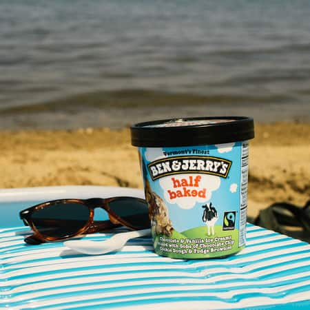 A Pint of Ben & Jerry's Half Baked sitting on a beach towel with sunglasses