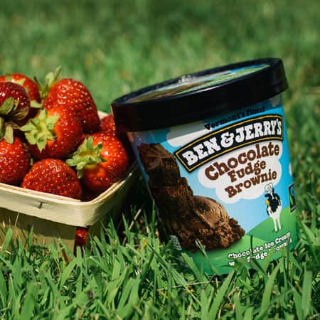 A Pint of Ben & Jerry's Chocolate Fudge Brownie with a carton of fresh strawberries