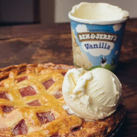 A Pint of Ben & Jerry's Vanilla with a scoop on top a freshly baked pie