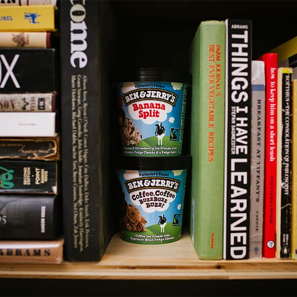 Ben & Jerry's Ice Cream on a bookshelf between books