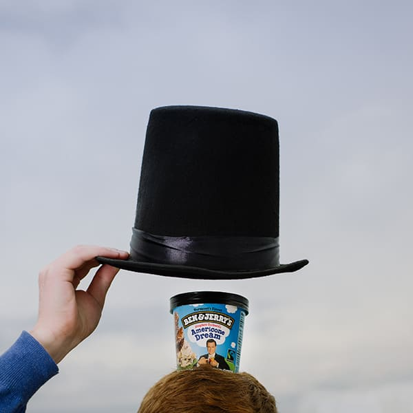 Ben & Jerry's Ice Cream on top a head with a hat over it
