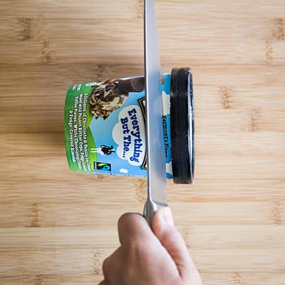 Ben & Jerry's Pint on its side with a knife cutting a slice of it