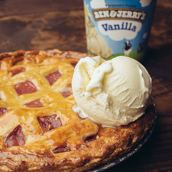 A piece of pie with a scoop of Ben & Jerry's Vanilla Ice cream