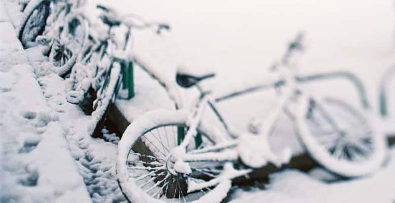 Bicycles on a bike rake covered in snow.