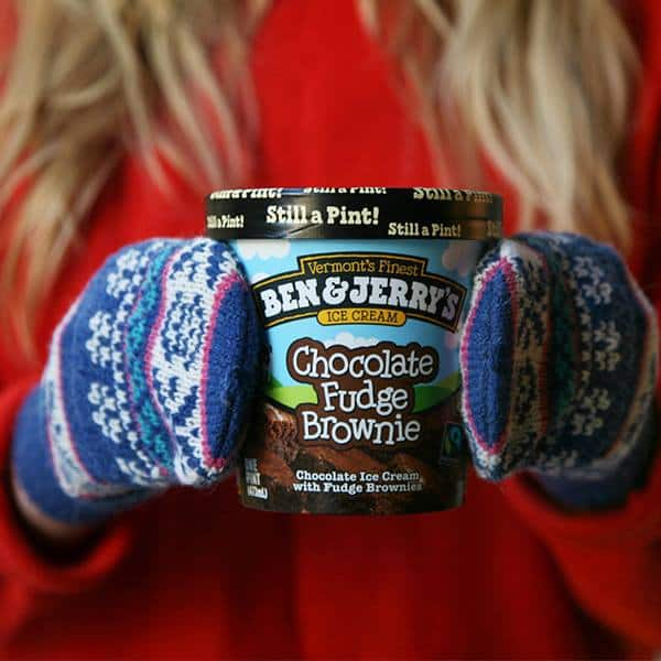 A Person holding onto a Ben & Jerry's Pint with mittens on their hands.
